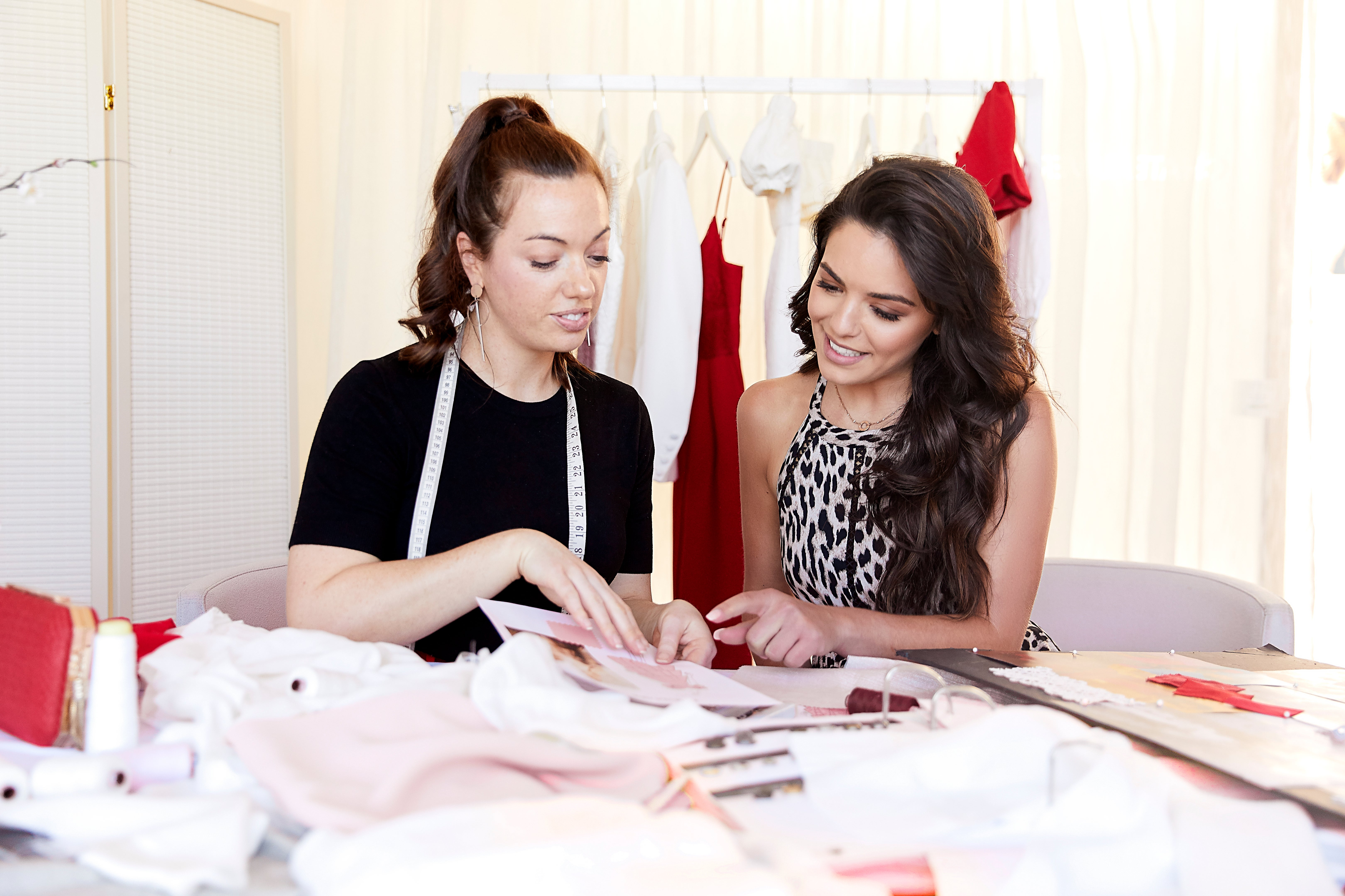 Two people looking at fabric for garment.