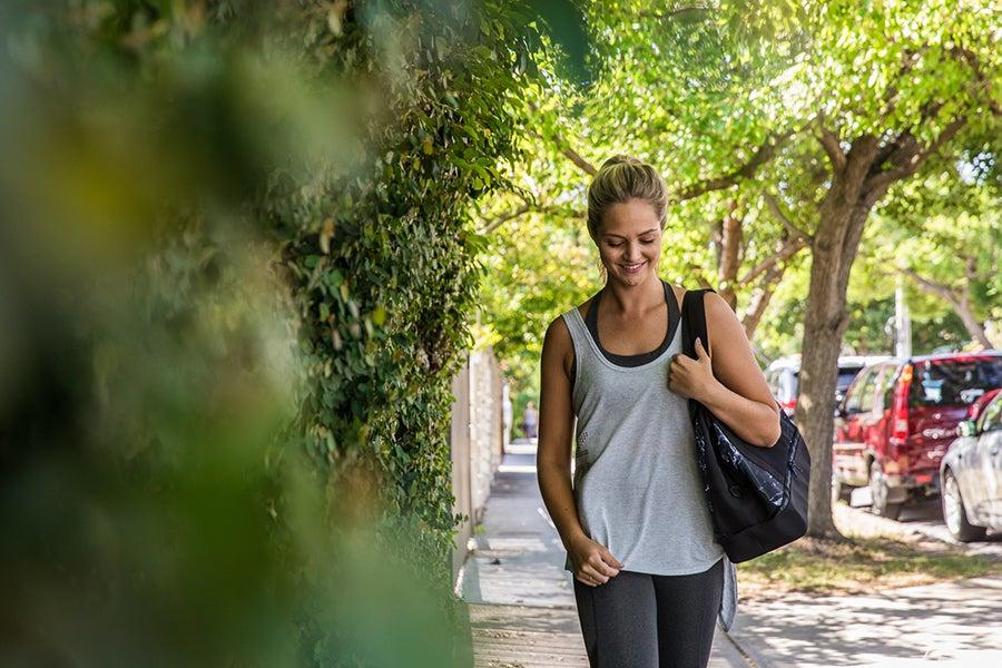 Girl wearing activewear walking down tree lined street