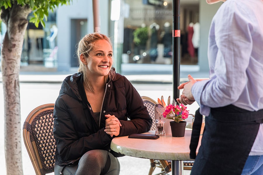 Girl wearing activewear sitting in cafe with waiter