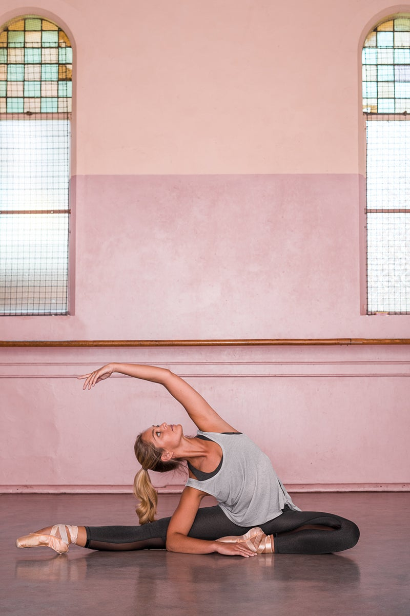 Girl stretching in studio wearing activewear