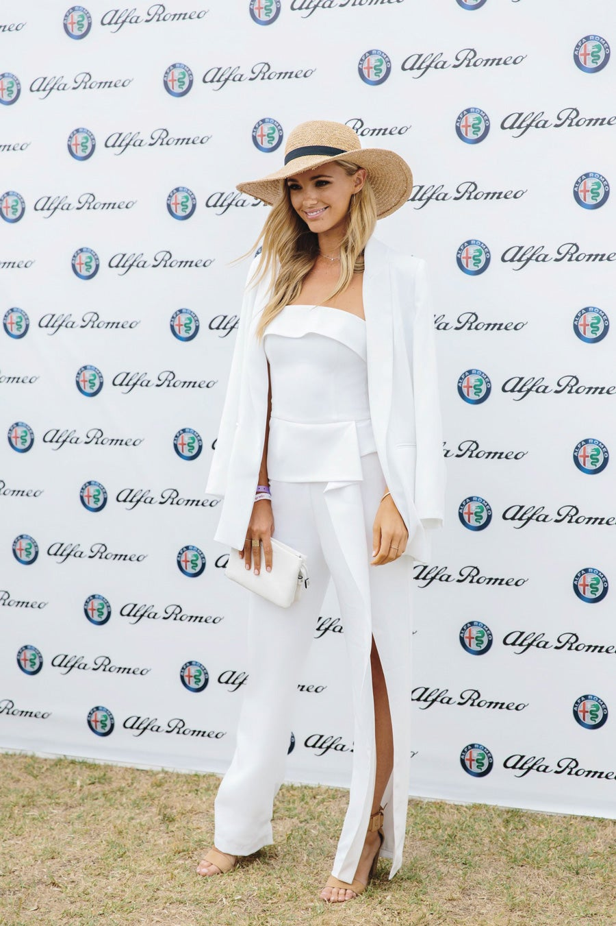 Girl in white outfit standing in front of media wall