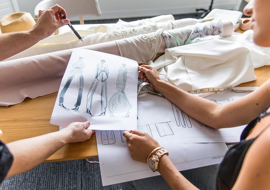 Two people looking at fashion illustration sketch with fabric rolls